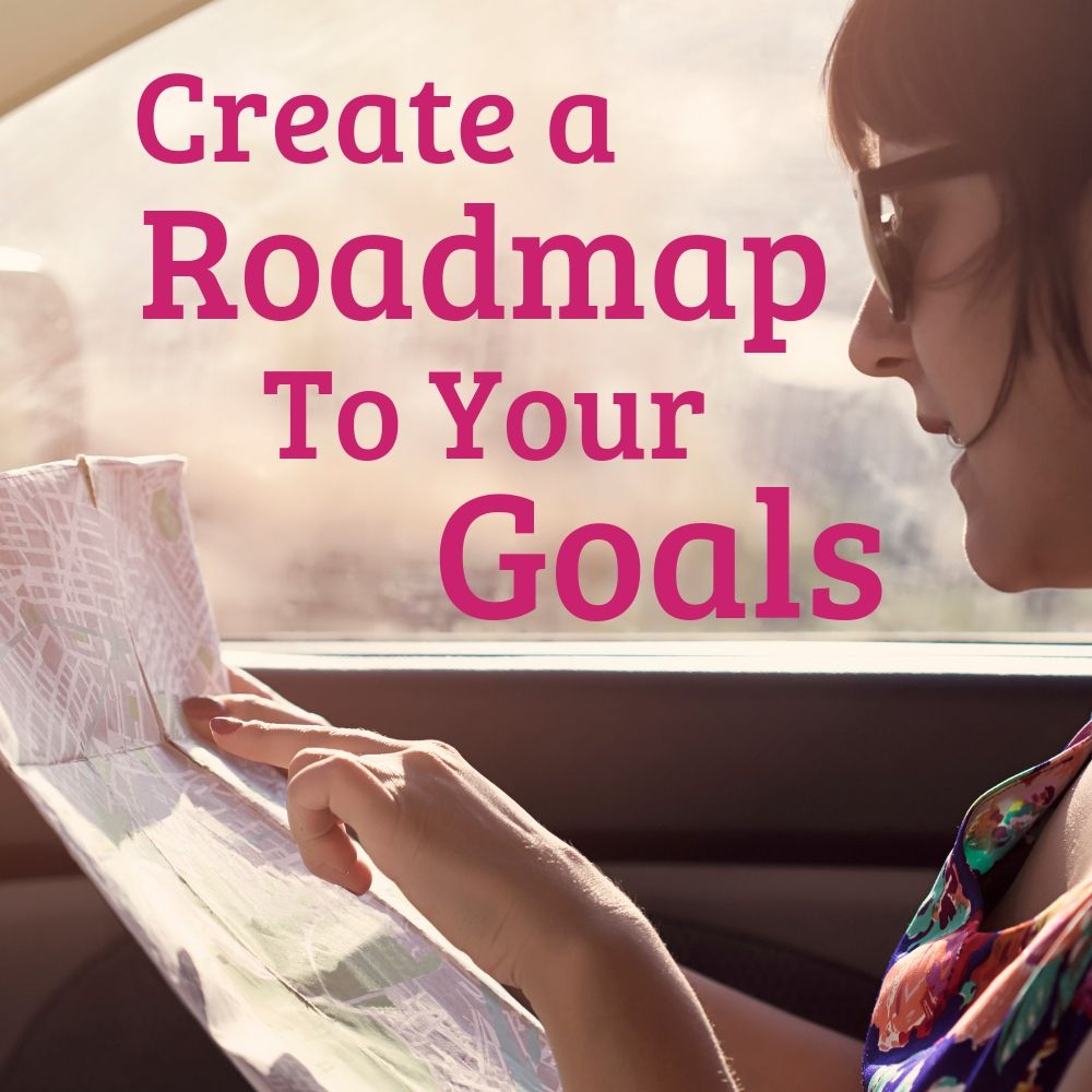 woman looking at map in car - create a roadmap to your goals