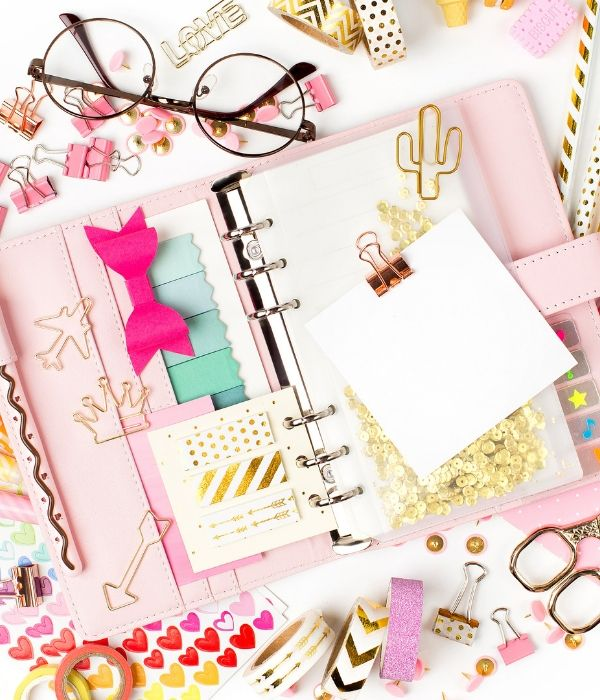 pink planner with accessories, glasses, washi tape, scissors, clips and pink bow; monthly planner themes to decorate with