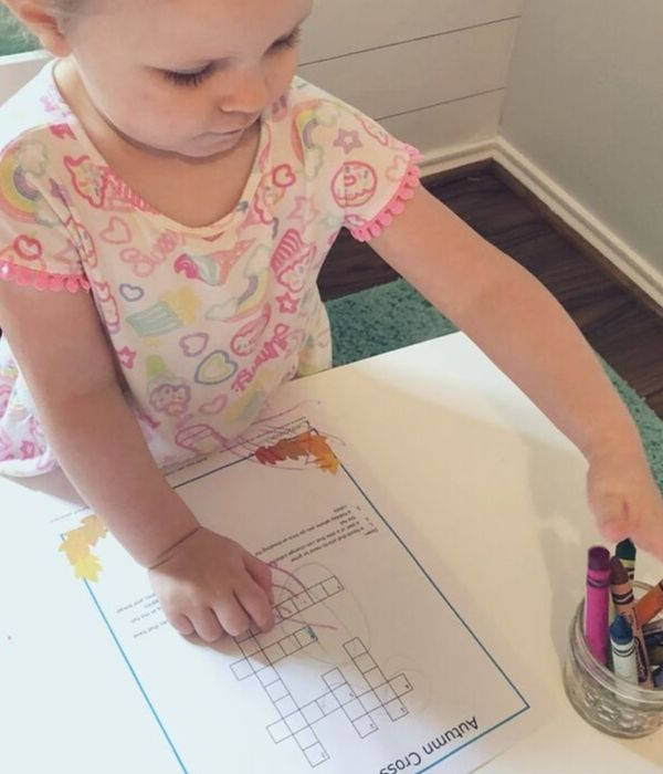 little girl coloring crossword puzzle