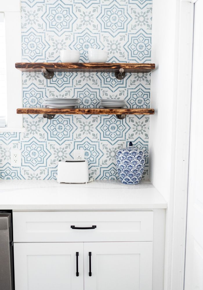 clean organized modern white kitchen cabinets, blue and white backsplash, wooden open shelves, with white and blue plactes