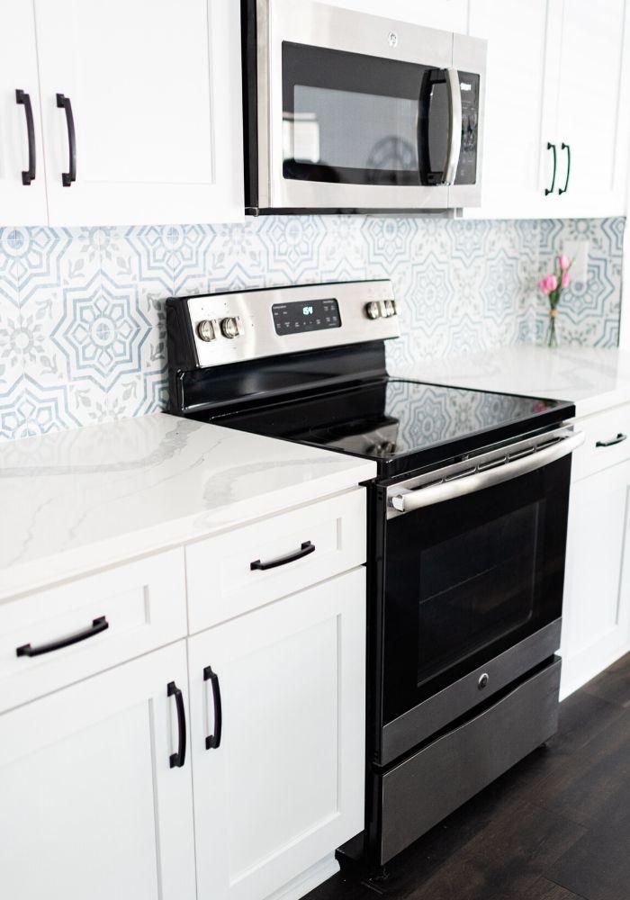 organized clean modern white kitchen cabinets, blue and white backsplash, oven