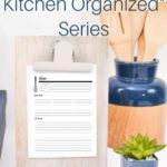 wooden clipboard with recipe card, bamboo utensils in blue holder; organized kitchen